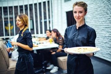 Kellnerin in Arbeitskleidung präsentiert ein Gericht in ihrer Gastronomie