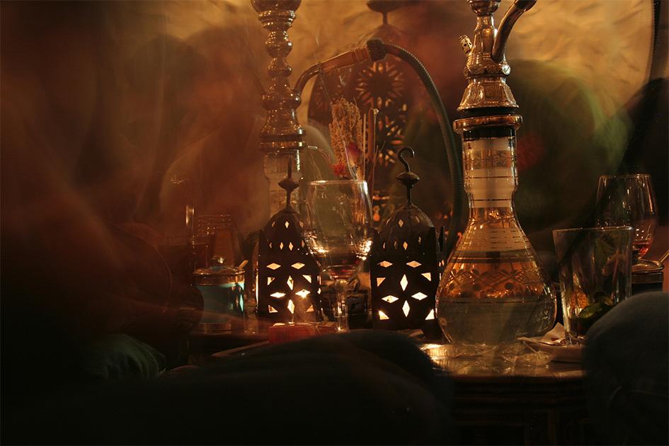 Lebendiges Treiben in einer Shisha-Bar mit Shishas und Getränken
