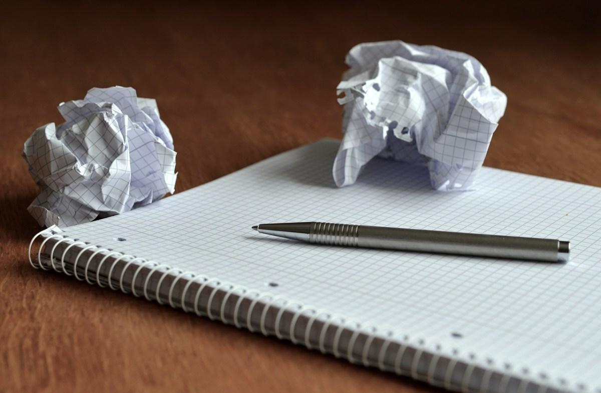 Ein Papierblock mit zerknülltem Papier und Stift