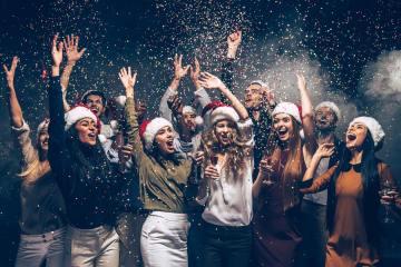Feierende Menschen mit Weihnachtshüten und Konfetti