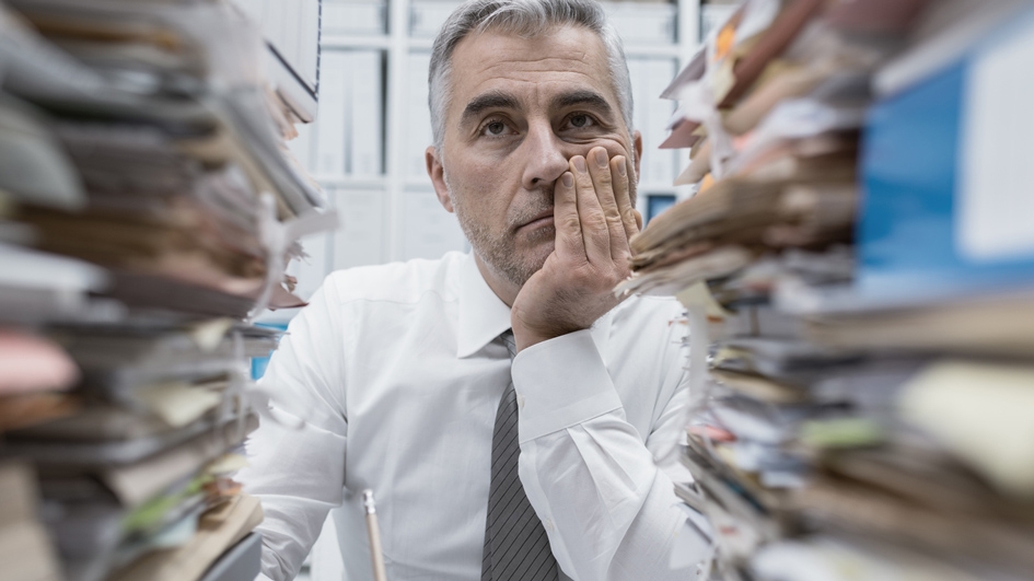 Ein Beamter in einer Behörde mit vielen Akten
