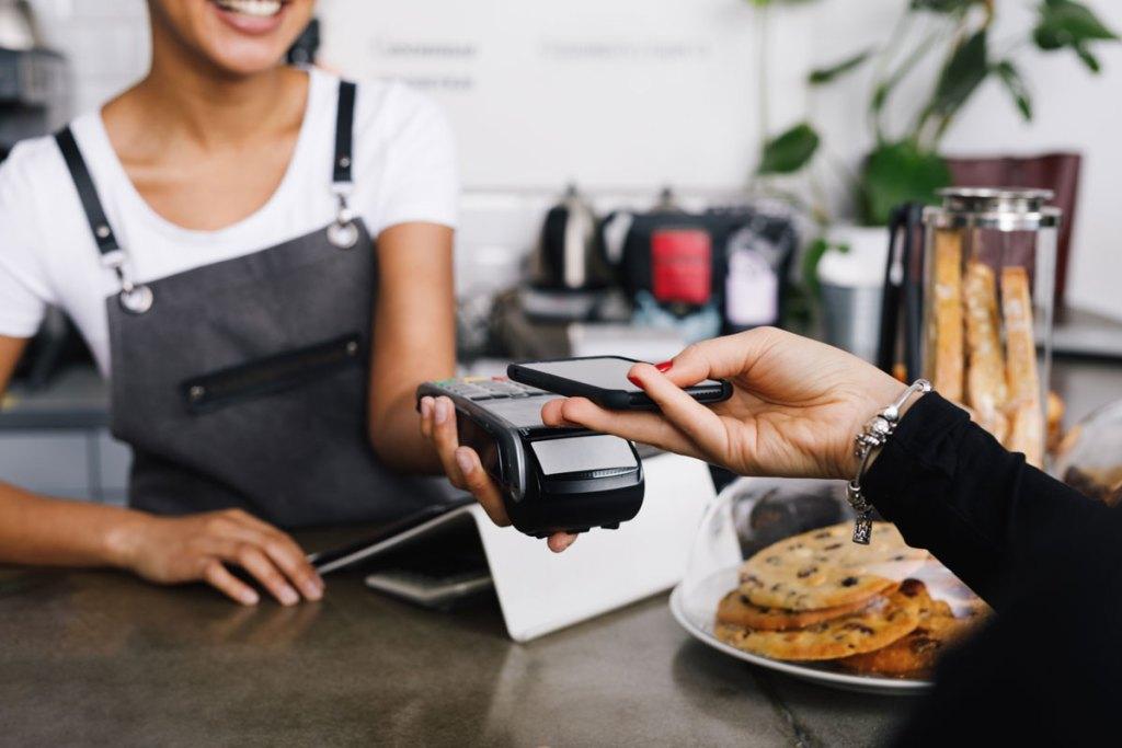 Junge Frau im Café mit Kreditkarte in der Hand schaut lächelnd auf ihr Smartphone
