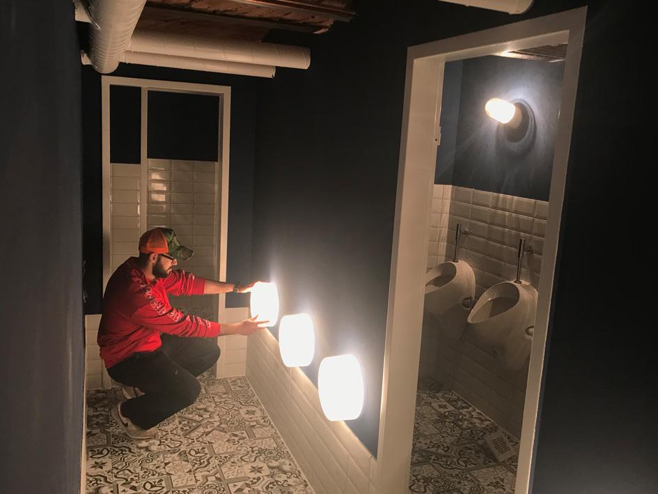 Gastro-Gründer Hussein bei der Lichtinstallation in den Toiletten seines Cafés