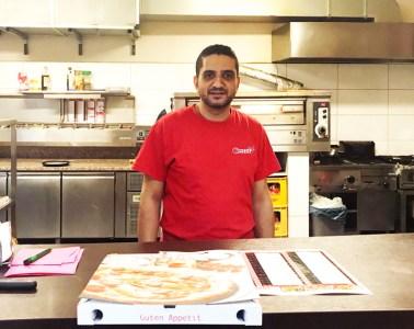 Khaled, der Besitzer von City Pizza, steht hinter dem Tresen seiner Pizzeria