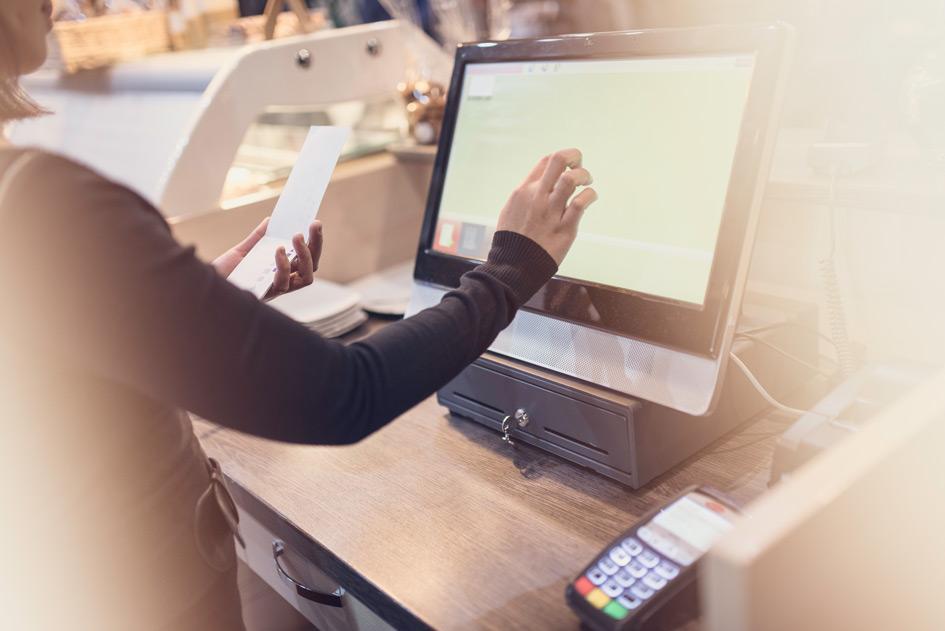 Ein PC-Kassensystem für die Gastronomie wird an einem Tresen von einer Kellnerin benutzt