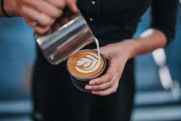 Eine Barista verziert mit Latte Art einen guten Kaffee
