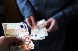 Hände überreichen einer anderen Hand viele fünfzig Euro-Scheine in einer dunklen Umgebung