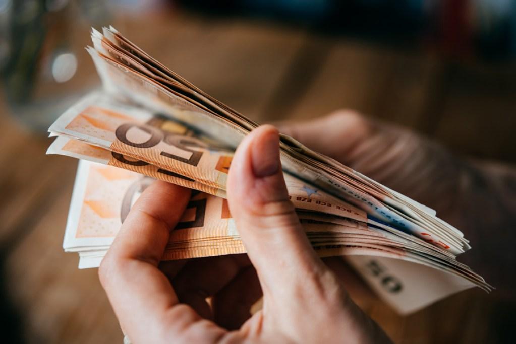 Eine Hand hält 50 Euro-Scheine und zählt sie