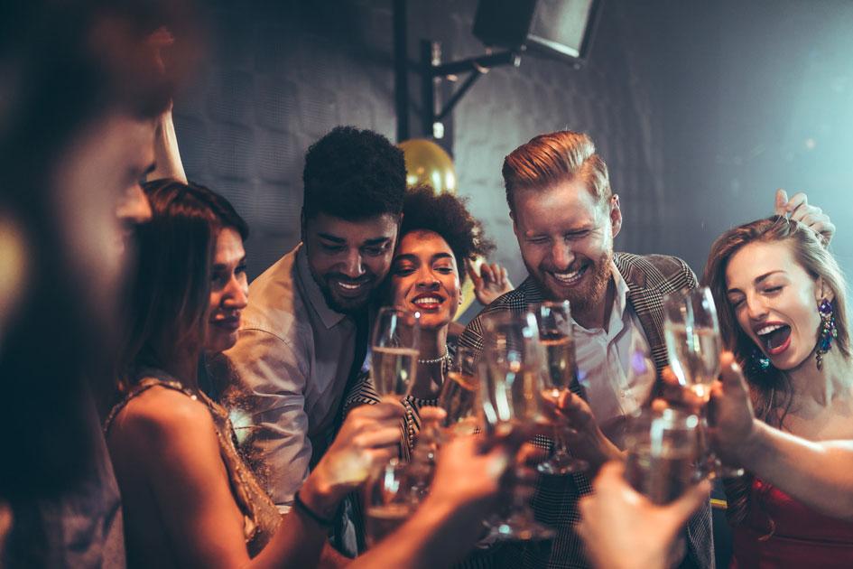 Eine Gruppe von feiernden Menschen stoßen in einer Bar an.