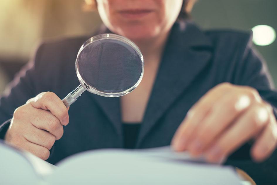 Eine Finanzprüferin hält eine Lupe vor Papiere nd prüft die Dokumente aufmerksam.