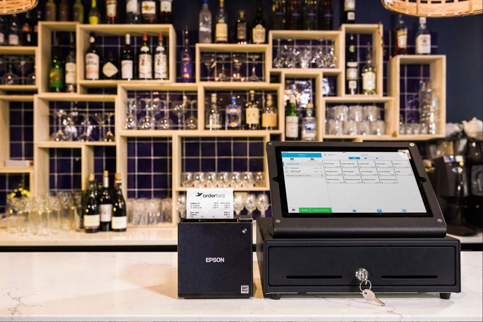 Die iPad-Kasse von orderbird mit Kassenlade und Drucker auf einem Tresen stehend. Dahinter Alkoholflaschen an der Wand.