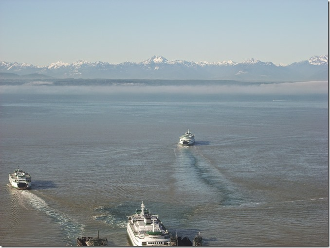Three ferries near the dock, in the distance are snow capped mountains