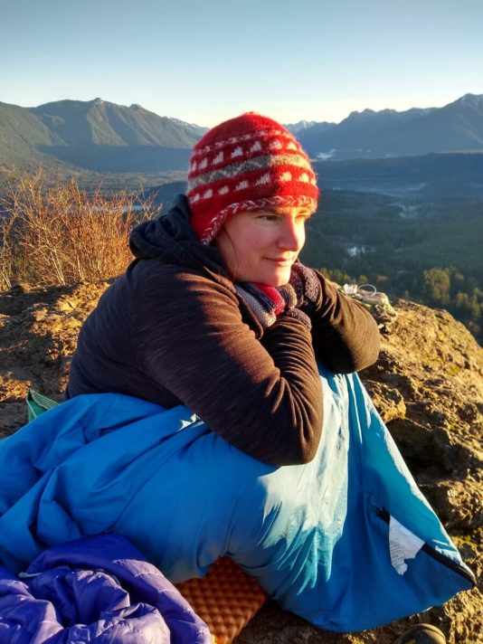 Woman in a hat and sleeping bag sitting on a rock