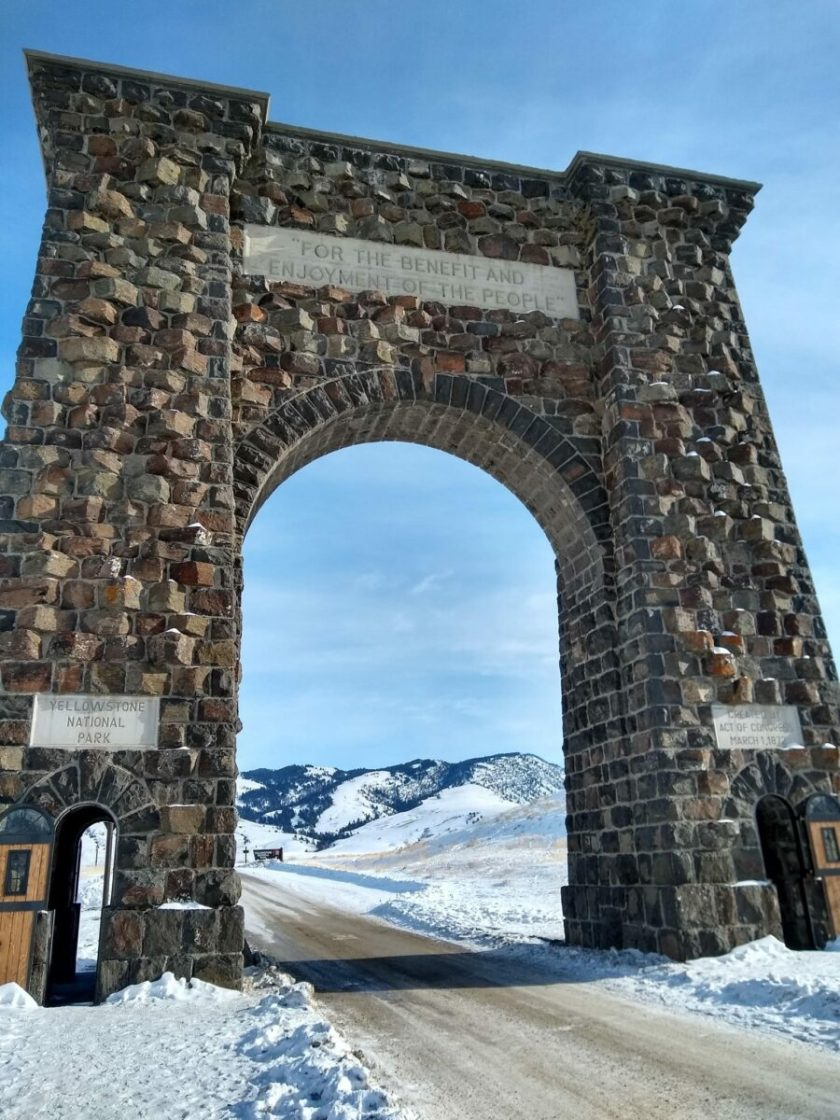 """Large stone arch over the road says Yellowstone National Park and """"For the Benefit and Enjoyment of the People"""""""