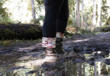 A big mud puddle with a woman's legs. She is wearing rubber boots and black leggings
