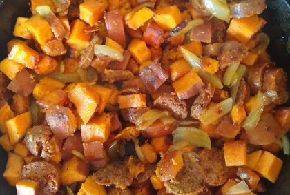 Chopped sweet potatoes, onion and vegetarian sausage in a cast iron pan