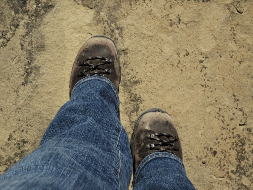 The bottom of a person's legs and feet on a dusty trail. The person is wearing jeans and worn leather hiking boots