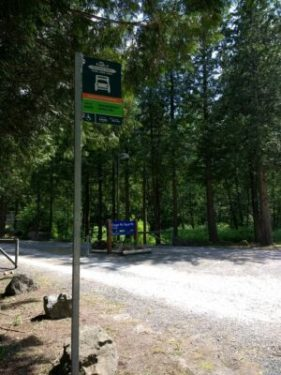 A parking lot at a trailhead in the forest with a bus stop.