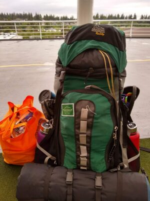 A large green backpack. It has a sleeping pad and two waterbottles attached to it, as well as a pair of sandals and a mug. An orange bag holds food.