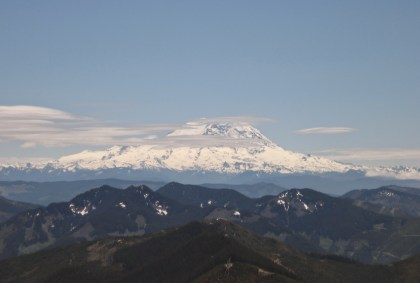 Mt Rainier, a high snow covered mountain, in the background surrounded by a few clouds on an otherwise sunny day. Smaller mountains are in the foreground