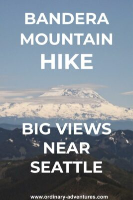 Mt Rainier, a high snow covered mountain, in the background surrounded by a few clouds on an otherwise sunny day. Smaller mountains are in the foreground. Text reads: Bandera Mountain hike, big views near Seattle