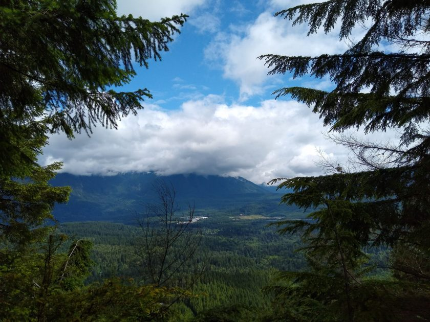 A view across a forested valley from Cedar Butte hike summit. It's a cloudy day with a bit of blue sky, and there are larger evergreen trees in the foreground