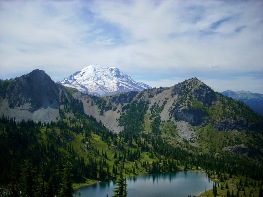 Mt Rainier in the distance behind a forested hillside surrounding a blue alpine lake