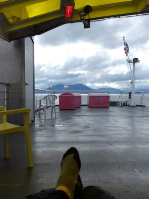 A person's feet are visible in the foreground on the deck of a ship under a cover. you can see the back of the ship, with an American flag, and water and mountains behind on the way to visit Glacier Bay national park