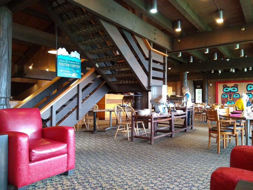 A lodge lobby has a staircase in the middle and red lounge chairs around. There is also a restaurant, with wooden tables and chairs and Tlingit art on the walls. The roof is made of wood and there is a patterned carpet
