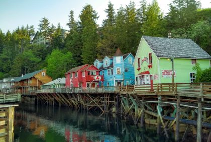 Spend part of a day in Ketchikan exploring the shops of historic creek street. Several brightly colored historic wooden buildings are built on wooden piers above the water. The water is calm and the buildings are reflected in it. There are evergreen trees behind the buildings on the hill