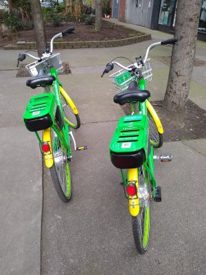 Two green and yellow electric bike share bikes parked next to each other on a Seattle sidewalk. Use a bike share e-bike to bike to alki beach!