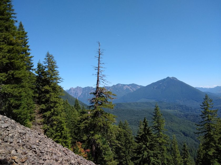 On the talus loop hike, the trail crosses a rock field. The rock field is in the foreground and evergreen trees in the background. in the distance are forested hills and higher mountains