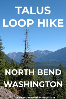 On the talus loop hike, the trail crosses a rock field. The rock field is in the foreground and evergreen trees in the background. in the distance are forested hills and higher mountains. Text reads: Talus loop hike North Bend Washington