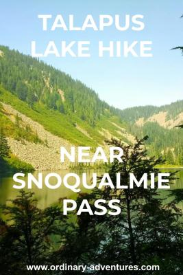 Talapus lake hike near Snoqualmie pass. It's a large alpine lake surrounded by forest and rocky mountains, which are reflected in the lake. There are evergreen trees in the foreground and it's a sunny day. Text reads: Talapus lake hike near snoqualmie pass