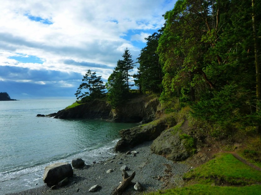 A small, gravel and rocky beach in a cove surrounded by rocks and green trees. It's a partly cloudy day with a bit of blue sky.