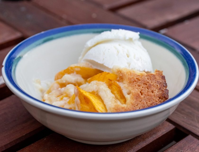 A white bowl with a blue rim holds peach cobbler and a scoop of vanilla ice cream