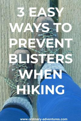 Two worn hiking boots seen from the person wearing them. A person's lower legs with blue leggings and gray and blue socks are also visible. The person is standing on a wooden path. Text reads: 3 easy ways to prevent blisters when hiking