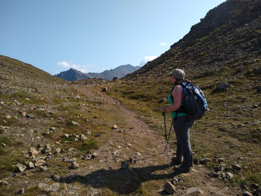 A woman stands on a trail looking at mountains in the distance. She has a blue backpack and is wearing a hat and sunglasses. She is using hiking poles and wearing gray long pants and a light green tank top