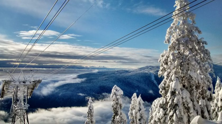 Snow covered trees and cables in the foreground. Clouds and forested hills below in the background on a partly cloudy day.