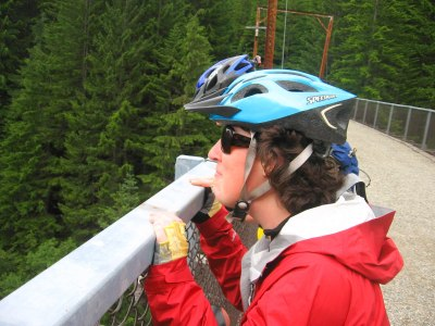 A women wearing sunglasses and a bike helmet looks out over the edge of a bridge. The bridge is graveled with a metal railing and surrounded by evergreen trees