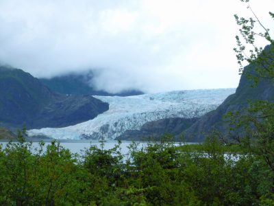 Things to do in Juneau include a visit to the Mendenhall Glacier, which is seen in the distance behind a lake. Around the glacier are rocky hillsides covered in thick, dark clouds. There are green trees and bushes in the foreground