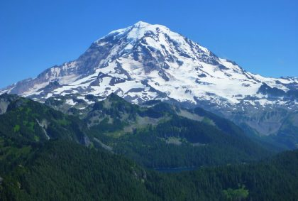 The Tolmie Peak Lookout hike has epic views of Mt Rainier. Here it is filling the frame against a clear blue sky with forested hillsides in the foreground.