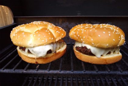 Two burgers with buns on a grill. They have sesame seeds on top adn the burgers are covered in melted cheese