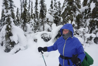 A person holding ski poles and dressed in lots of warm clothes on a snowy day in the forest. The person is smiling.