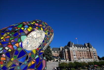 Walking around the inner harbor is one of the best things to do in Victoria! Here a colorful orca sculpture is in the foreground and a large stone hotel in the background. It's a blue sky day.