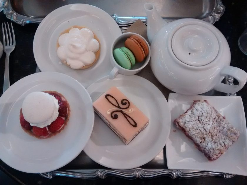 A try with a white tea pot, four plates with pastries and a small plate with two cookies