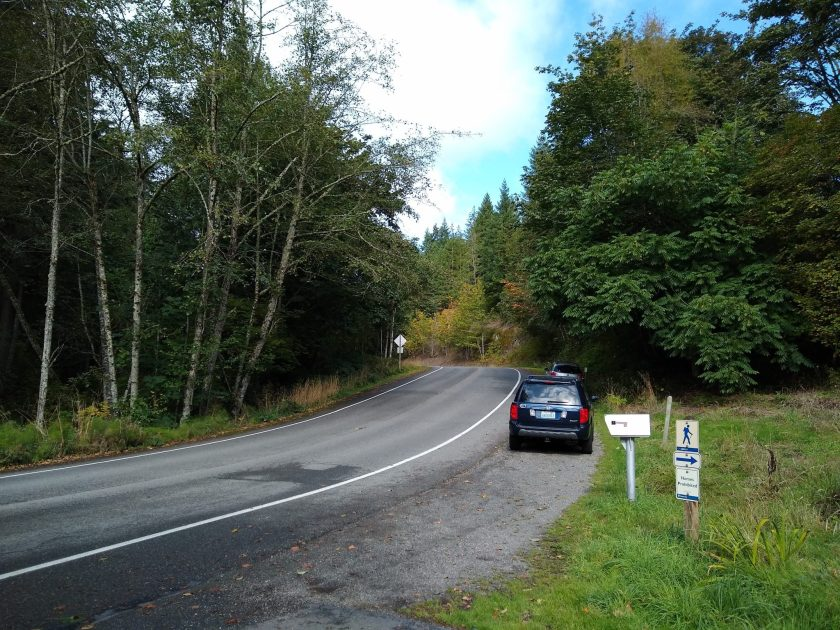 A paved, two lane road through the forest. There is a blue SUV parked on the side of the road. There is also a mailbox and a small hiker sign with an arrow to the right