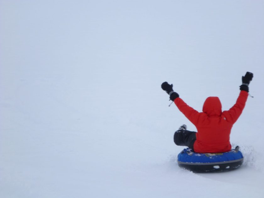 A person on a foggy winter day riding downhill on a snow tube. Their hands are in the air and they are wearing black snow pants, a red jacket and black mittens
