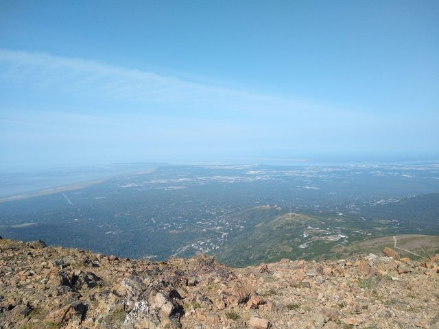 In the foreground are rocks and a drop off. In the distance and far below is the city of Anchorage, Alaska. This hike is one of the best things to do in Alaska