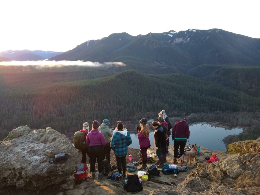 a group of women stand on a ledge to watch the sunrise on a winter hike. There is a lake below them and mountains in the distance